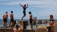 Beachgoers enjoy a summer day at Coogee Beach in Sydney