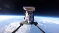The first pack of haggis to ever be launched into space floats in atmosphere attached to a contraption device