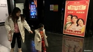 """People walk past a poster for Chinese movie """"Hi Mom"""" at a cinema in Beijing"""