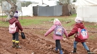 Internally displaced Syrian children walk in mud near tents at a camp in northern Aleppo near the Syrian-Turkish border.