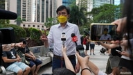 Pro-democracy activist Avery Ng gestures to the media before a trial outside the court in Hong Kong