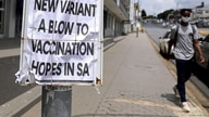 A man walks past newspaper billboards during the coronavirus disease (COVID-19) outbreak in Johannesburg