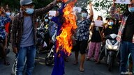 FILE - Protesters against Myanmar's junta burn the flag of the Association of Southeast Asian Nations (ASEAN), in Mandalay.