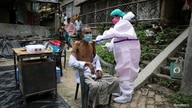 A villager receives a dose of COVISHIELD vaccine during a door-to-door vaccination and testing drive at Uttar Batora Island