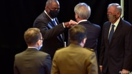 U.S. Defense Secretary Lloyd Austin fist bumps Singapore Senior Minister Teo Chee Hean, after speaking at the IISS Fullerton Lecture in Singapore