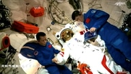 Chinese astronauts Tang Hongbo and Liu Boming work with a spacesuit at Tianhe core module of China's space station