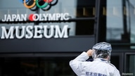 A policeman holds onto his hat because of strong wind gusts caused by a tropical storm Nepartak in front of the Japan Olympic Museum in Tokyo