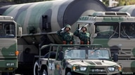 FILE PHOTO: PLA soldiers salute in front of nuclear-capable missiles during a parade in Beijing