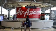 A woman walks past an AirAsia counter at Kuala Lumpur International Airport in Sepang, Malaysia, July 22, 2019. Picture taken…