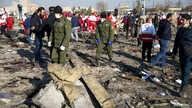 Security officers and Red Crescent workers are seen at the site where the Ukraine International Airlines plane crashed after…
