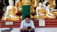 A man wears a face mask as he uses his phone at Shwedagon Pagoda in Yangon, Myanmar January 31, 2020. REUTERS/Ann Wang