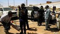 Security personnel stand near a car damaged after an explosion targeting the motorcade of Sudan's Prime Minister Abdalla Hamdok…