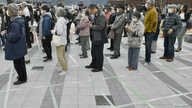 People wearing protective face masks, following an outbreak of the coronavirus disease (COVID-19), form a line while keeping…