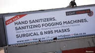 A worker attaches a billboard, advertising sales of hand sanitizer and masks, to a building ahead of a 21 day lockdown aimed at…