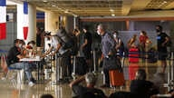 Visitors queue to register their documents with French embassy officer before their chartered flight back to their country,…