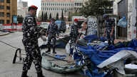 Lebanese security forces pull down tents as they clear away a protest camp and reopened roads blocked by demonstrators since…
