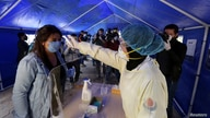 A medic from Hezbollah's islamic health unit checks the temperature of a woman, inside a tent facility to test for coronavirus…