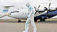 A member of a medical team wearing protective suits clean the airfield, to prevent the spread of the coronavirus disease (COVID…