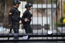 Members of Venezuelan security forces are seen on the background as documents regarding a proposed amnesty law for members of the military, police and civilians stand in a fence in Caracas, Venezuela, January 27, 2019.