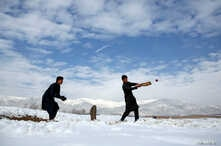 FILE -- Afghan men play cricket on a field covered in snow on the outskirts of Kabul, Afghanistan, Dec. 16, 2017.