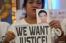 A woman displays a picture of her son, a drug war victim, and a placard during a protest against the war on drugs by President Rodrigo Duterte in Quezon city, Metro Manila in Philippines, Aug. 28, 2018.