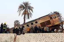 FILE - People gather at the site of a train derailment near Beni Suef, Egypt, Thursday, Feb. 11, 2016 that  injured dozens of people were injured as it was traveling north toward Cairo. Railroad accidents due to negligence are common in Egypt.