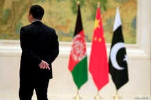 FILE - A member of the security personnel stands guard next to, from left, Afghan, Chinese and Pakistani flags during the first China-Afghanistan-Pakistan Foreign Ministers' Dialogue in Beijing, China, Dec. 26, 2017.