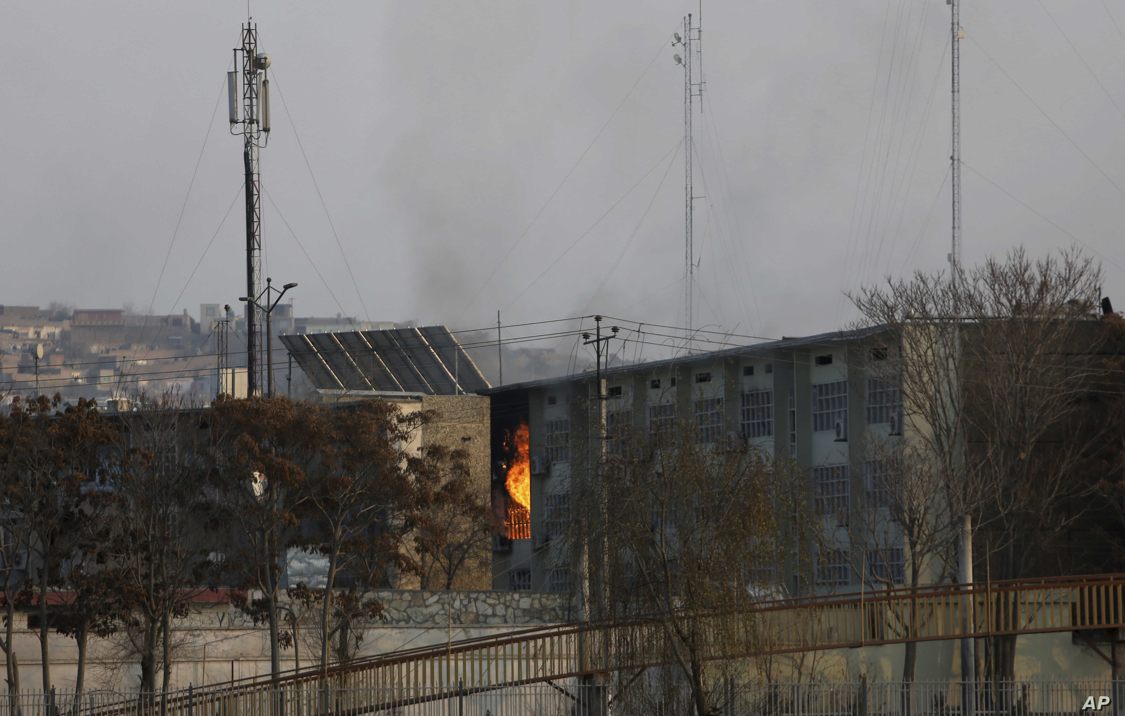 Flames rise from a government building after an explosion and attack by gunmen, in Kabul, Afghanistan, Monday, Dec. 24, 2018.