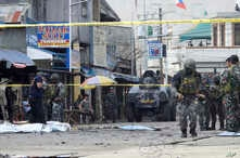 Police investigators and soldiers attend the scene after two bombs exploded outside a Roman Catholic cathedral in Jolo, the capital of Sulu province in southern Philippines, Jan. 27, 2019. Two bombs minutes apart tore through a Roman Catholic cathedr