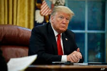 FILE - President Donald Trump listens to a question during an interview in the Oval Office of the White House, in Washington, Oct. 16, 2018.