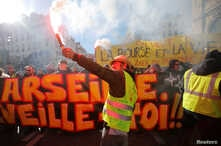 "A protester wearing a yellow vest holds a flare as he takes part in a demonstration of the ""yellow vests"" movement in Marseille, France, January 26, 2019."
