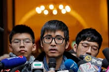 Pro-democracy activist Alex Chow, center, speaks to reporters outside the Court of Final Appeal in Hong Kong, Feb. 6, 2018. Hong Kong's highest court Tuesday overturned prison sentences for three young pro-democracy activists convicted for their role