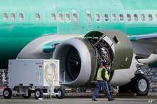 A worker walks past an engine on a Boeing 737 MAX 8 airplane being built for American Airlines at Boeing Co.'s Renton assembly plant, March 13, 2019, in Renton, Wash.