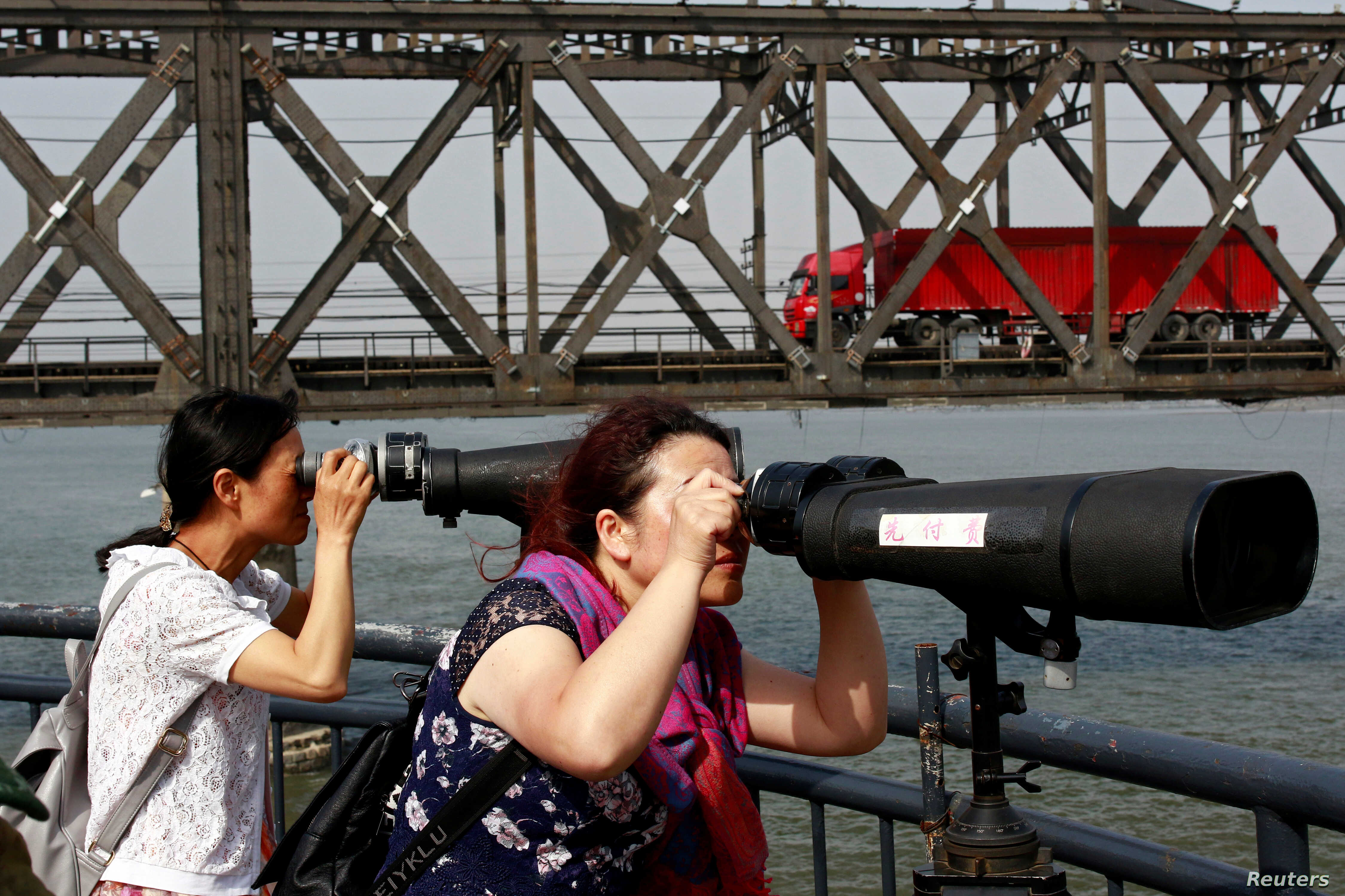 Chinese visitors look through binoculars towards North Korea from the Broken Bridge, as a truck crosses the Friendship Bridge on the Yalu river from Sinuiju, North Korea to Dandong, Liaoning province, China, May 24, 2018.
