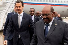 In this photo released by the Syrian official news agency SANA, Syrian President Bashar al-Assad, left, meets with Sudan's President Omar al-Bashir in Damascus, Syria, Dec. 16, 2018.