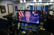 President Donald Trump is seen on monitors in the briefing room of the White House, as he gives a prime-time address in the Oval Office, Jan. 8, 2019.