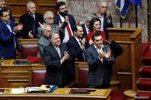 Greek Prime Minister Alexis Tsipras and members of his government applaud after a vote on an accord between Greece and Macedonia changing the former Yugoslav republic's name in Athens, Greece, Jan. 25, 2019.