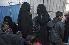 Two women (C), reportedly wives of Islamic State (IS) group fighters, wait with other women and children at a makeshift clinic at the Internally Displaced Persons (IDP) camp of al-Hol in al-Hasakeh governorate in northeastern Syria,on February 7, 201
