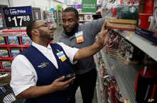 FILE - A Walmart employee, left, is coached by a trainer to use an inventory app at a Walmart store in North Bergen, New Jersey, Nov. 9, 2017.