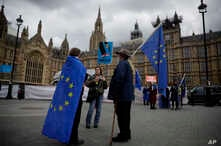 Anti-Brexit and remain in the European Union supporters stand  near Houses of Parliament in London, April 3, 2019. After failing to win Parliament's backing for her Brexit blueprint, Britain's Prime Minister Theresa May changed gears, saying she woul