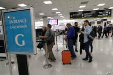 Passengers wait at the security entrance to Concourse G at Miami International Airport in Miami, Jan. 11, 2019.