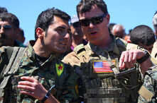 A file photo taken on April 25, 2017 shows a US officer from the US-led coalition, speaking with a fighter from the Kurdish People's Protection Units (YPG) at the site of Turkish airstrikes near northeastern Syrian Kurdish town of Derik.
