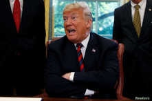 U.S. President Donald Trump talks to reporters about the killing of journalist Jamal Khashoggi in Turkey during a bill-signing ceremony at the White House in Washington, Oct. 23, 2018.
