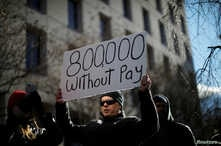 """FILE - A demonstrator holds a sign, signifying hundreds of thousands of federal employees who won't be receiving their paychecks as a result of the partial government shutdown, during a """"Rally to End the Shutdown"""" in Washington, Jan. 10, 2019."""