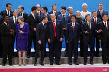 President Donald Trump, front center, listens to France's President Emmanuel Macron as they pose with world leaders for a group picture at the start of the G20 Leader's Summit inside the Costa Salguero Center in Buenos Aires, Argentina, Friday, Nov.