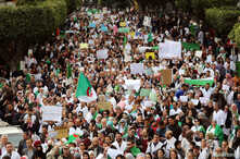 Health workers carry national flags and banners as they march during a protest calling on President Abdelaziz Bouteflika to quit, in Algiers, Algeria March 19, 2019.