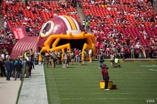 Fans await the entrance of the Washington Redskins through a large, inflatable helmet, as the Washington Redskins host the Jacksonville Jaguars, at FedEx Stadium in Landover, Maryland, Sept. 14, 2014. (VOA / Frank Mitchell)
