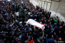 Mourners and Palestinian Hamas members carry the body of their comrade, who was killed in an Israeli airstrike, during his funeral in Gaza City December 9, 2017.