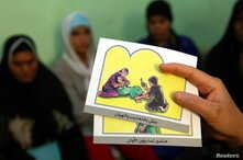 A counsellor holds up cards used to educate women about female genital mutilation (FGM) in Minia June 13, 2006.  The practice of FGM dates back over two thousand years in Egypt and is widely practiced in all levels of society for Muslims and Christia