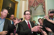 Treasury Secretary Steve Mnuchin, center, speaks with reporters as he departs the Republican policy luncheon on Capitol Hill, Jan. 15, 2019.